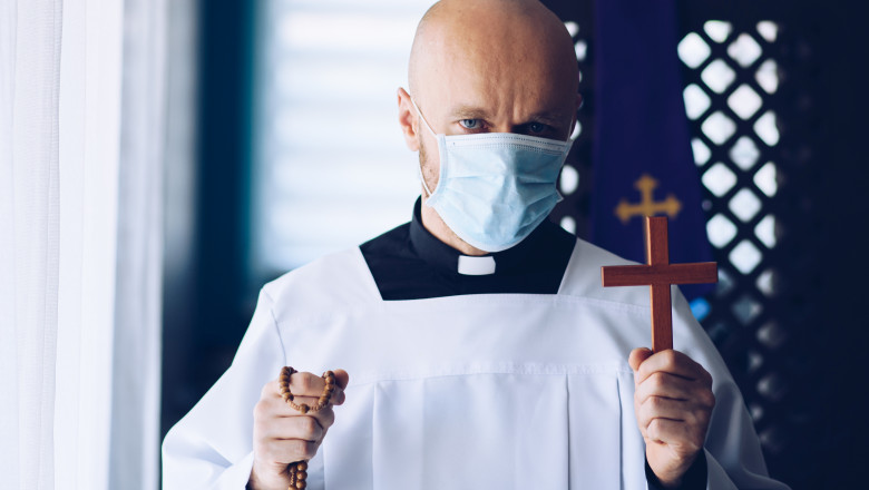 Man priest in medical mask praying with cross and rosary.