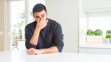 Handsome hispanic man wearing casual sweater at home tired rubbing nose and eyes feeling fatigue and headache. Stress and frustration concept.