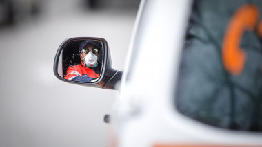 Bucharest, Romania - April 1, 2020: Ambulance driver seen in the side mirror of the vehicle.