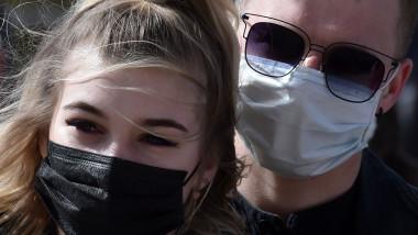 Doua persoane poarta masca de protectie impotriva raspandirii COVID-19