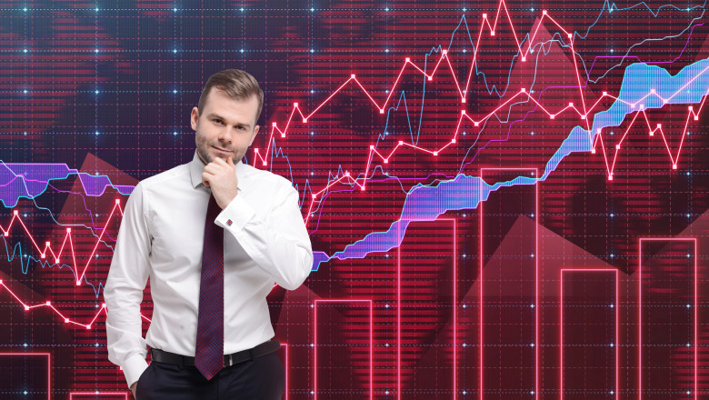 Male trader thinking in front of a colorful forex graph