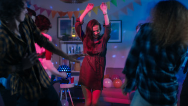 At the College House Party: Young Girl Dances in the Middle of a Circle of People. Diverse Group of Friends Have Fun, Dancing and Socializing. Disco Neon Strobe Lights Illuminating Room.