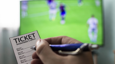Men's hands with a ticket bookmaker's office, on TV show football, Champions League, sports betting, close-ups