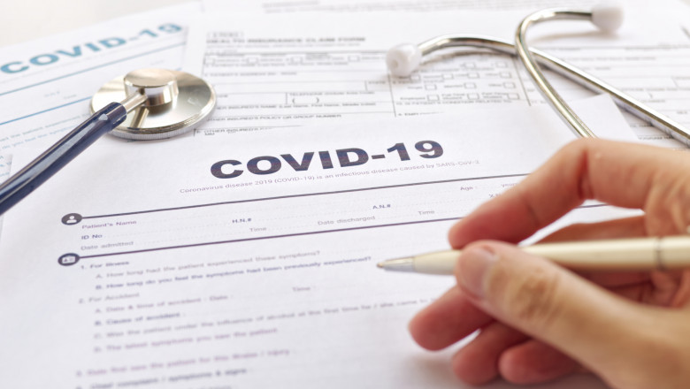 """COVID-19 Health insurance concept. Blurring of hand holding pen and Stethoscope on health form. Focus on """" COVID-19 """""""