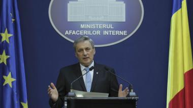 ministrul de Interne, Marcel Vela, gesticulează la pupitru, în cadrul unei declaraţii