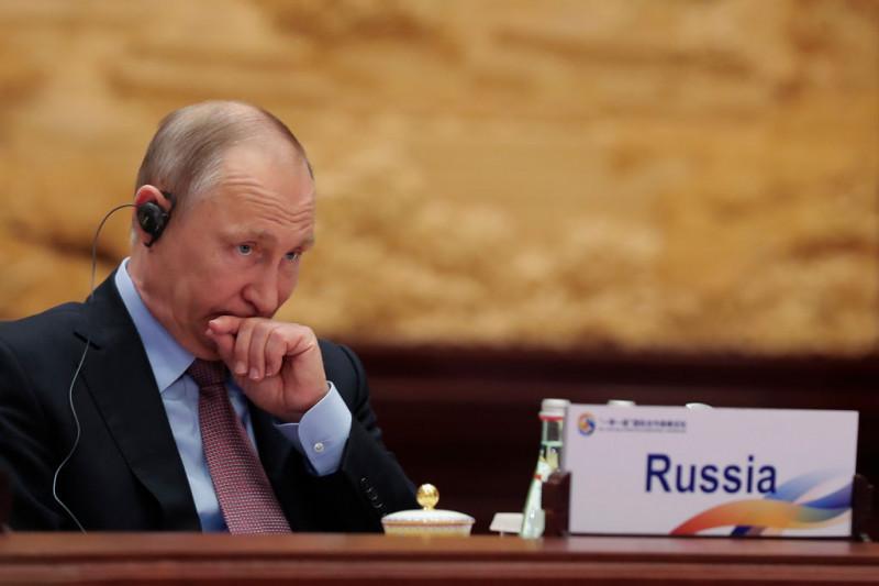 preşedintele Rusiei, Vladimir Putin, cu o casă pe cap, ascultă