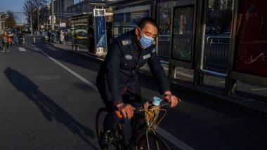 Un barbat cu masca se deplaseaza cu bicicleta pe strazile pustii dintr-un oras din China