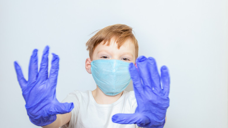 A seven-year-old boy in a medical mask and latex gloves extended his arms in front of him on a white background. Social distance, caronavirus quarantine concept