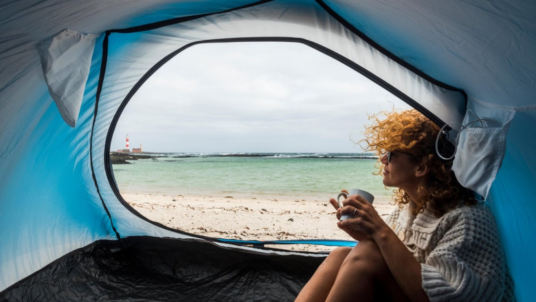 lonely beautiful woman sitting on the tent looking outside. wind on the hair and camping on the beach near the colors of water and shore. freedom and