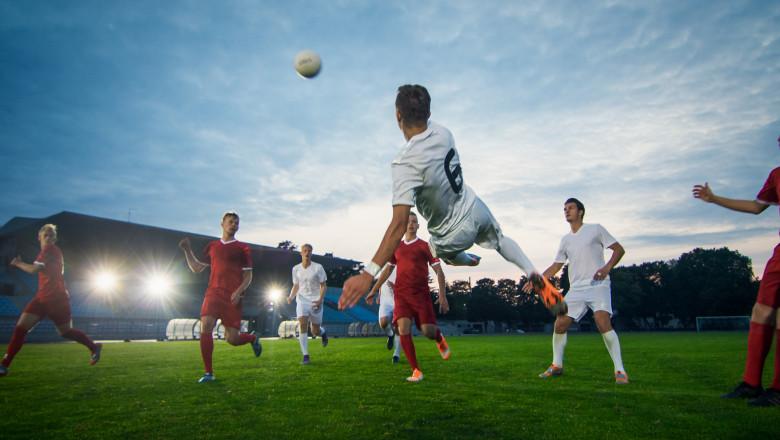 sportivi joacă fotbal pe teren