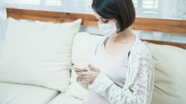 GettyImages-femeie însărcinată uitându-se pe telefon
