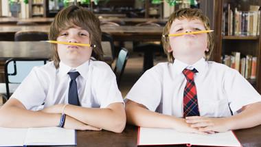 elevi de şcoală ţin creioanele pe buze