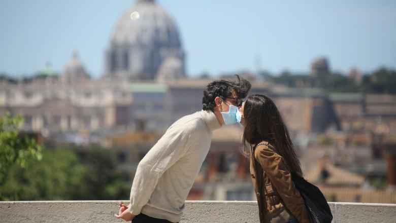 tineri îndrăgostiţi la Roma, se pupă cu măşti pe faţă
