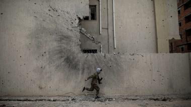 război civil Libia, luptător al forţelor guvernamentale fuge de focul lunetiştilor