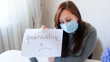 Young woman in a medical protective face mask at home. Quarantine inscription in the hands of a sadness girl. Pandemic mood.