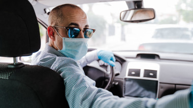 man driving a car wearing protective mask and gloves during pandemic coronacirus covid-19