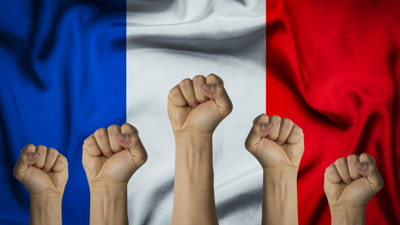 Hands raised up and clenched into a fist against the background of the flag of France. Concept of the unity of the French people, revolution, revival, riot