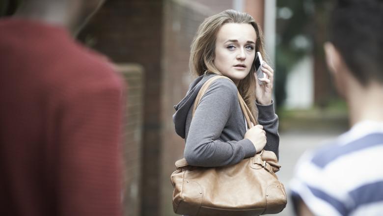 Teenage Girl Using Phone As She Feels Intimidated