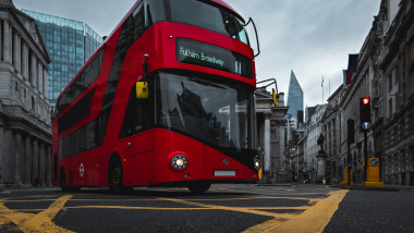 Double decker, red London bus on the move at Bank Tube Station