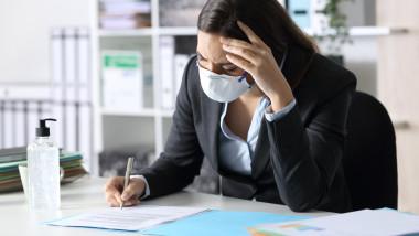 femeie la birou cu mască de protecție