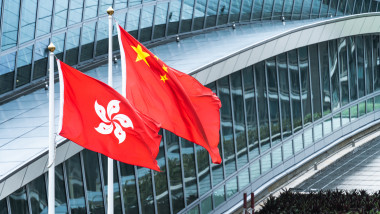 Hong Kong and mainland China national flags stand together with copy space. Nation symbol, countries political conflict concept