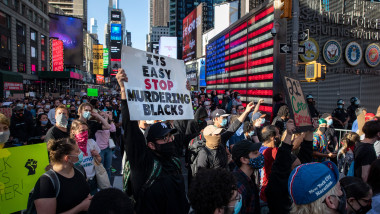 NEW YORK, NEW YORK - MAY 31: Black Lives Matter protesters kneel in Times Square during a march to honor George Floyd in Midtown Manhattan on May 31, 2020 in New York City. Protesters demonstrated for the fourth straight night after video emerged of a Minneapolis police officer, Derek Chauvin, pinning George Floyd's neck to the ground. Floyd was later pronounced dead while in police custody after being transported to Hennepin County Medical Center. The four officers involved have been fired and Chauvin has been arrested and charged with 3rd degree murder. (Photo by John Moore/Getty Images)