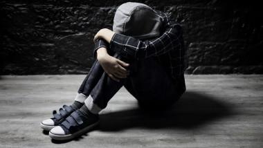 un copil sta cu capul pe genunchi