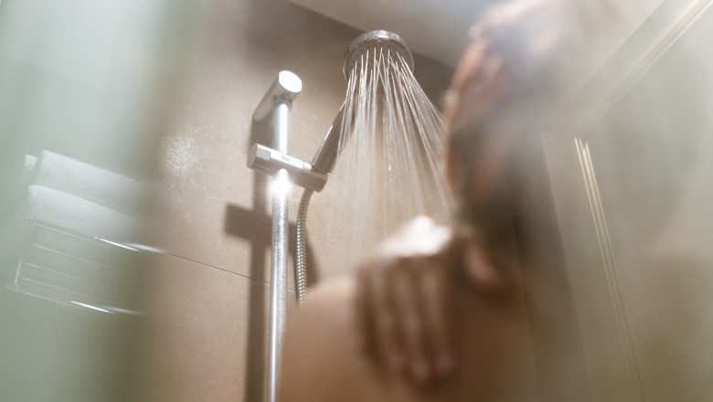 Young Asian woman taking a shower in the bathroom with hot steam filling the room - Lifestyle, bathe and hygiene concept