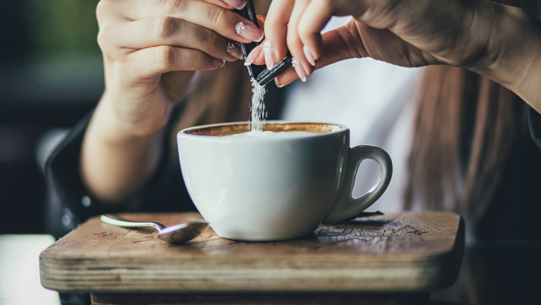 The girl's hand pours sugar into her coffee. Close up