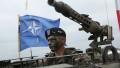 militar NATO cu o mitralieră și steagul NATO în fundal