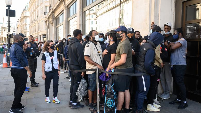 oamenii stau la coada in fata unui magazin din Londra dupa redeschidere pandemie