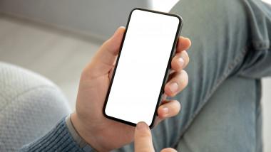 Un barbat tin in mana un telefon cu ecranul blocat