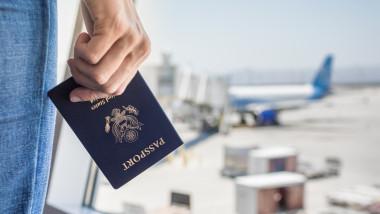 O femeie aflata intr-un aeroport tine in mana un pasaport