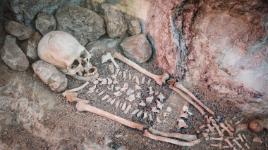 Skeleton of a primitive man inside a cave.