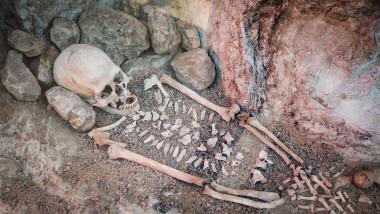 Skeleton of a primitive man inside a cave.