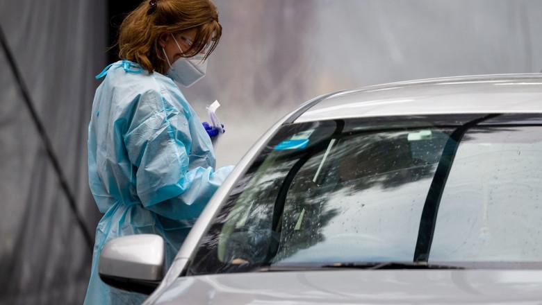 O asistentă medicală în echipament de protecție testează o persoană la Covid-19 dintr-o mașină.