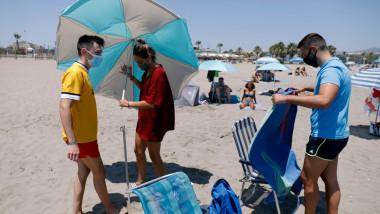 Tineri pe plaja din Malaga purtând măști de protecție