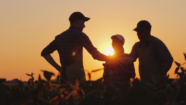 A group of farmers in the field, shaking hands. Family Agribusiness