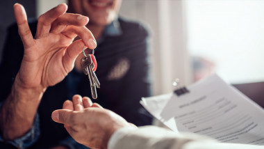 Real estate agent passing keys to his client