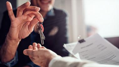 agent imobiliar dă cheile locuinței clientului său