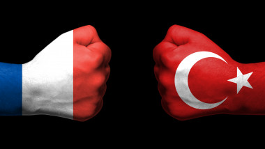 Flags of France and Turkey painted on two clenched fists facing each other on black background/ Denmark and Turkey relations concept