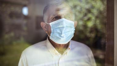 O persoana in varsta poarta masca pentru a se feri de coronavirus