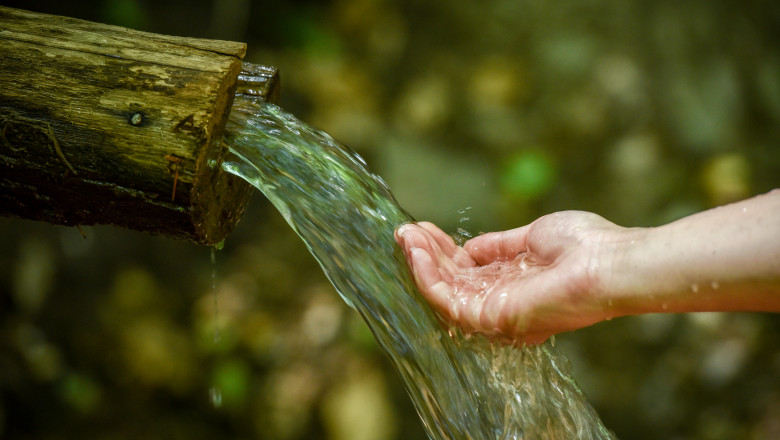 Drinking clean spring water in nature with hands cupped