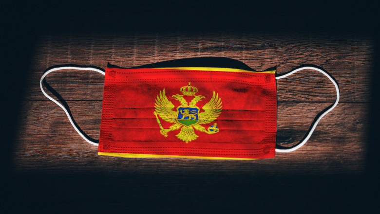 "Montenegro National Flag at medical, surgical, protection mask on black wooden background. Coronavirus Covid""u201319, Prevent infection, illness or flu. State of Emergency, Lockdown..."