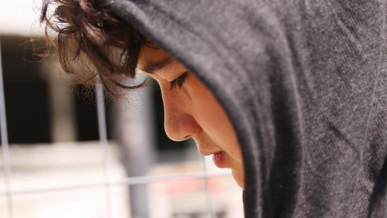 Sad troubled hispanic school boy teenager wearing a hoodie posing outdoor