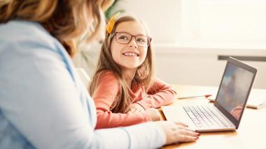 un adult sta cu o fetita la masa in fata laptopului