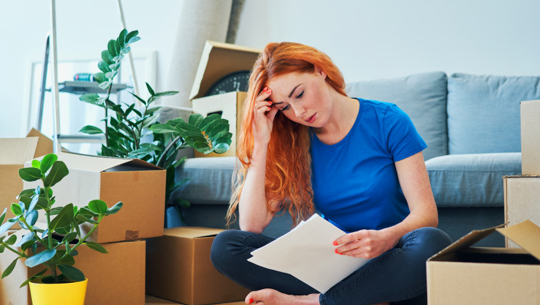 Worried young woman sitting on floor in apartment looking at bills and rental agreement