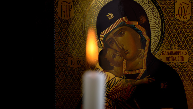Orthodox icon of the Mother of God and baby Jesus and a blurred burning candle in front of icon