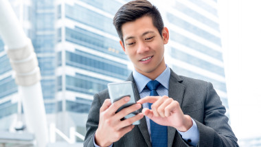 Young handsome Asian businessman using mobile phone surfing internet