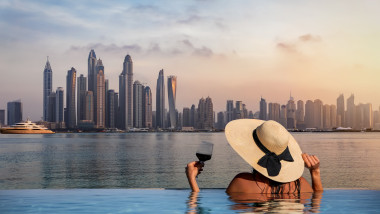 A woman with a hat stands at the edge of a pool and enjoys the view to the skyline of the Dubai Marina